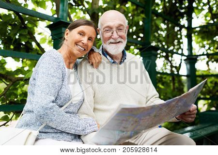 Affectionate mature spouses with map guide sitting in park on summer day