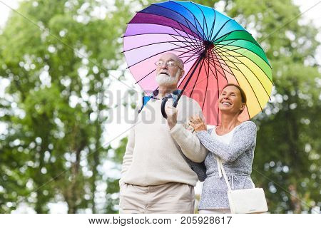 Senior tourists with colorful umbrella sightseeing in amusement park