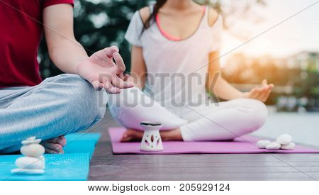 Closeup hands Young man and woman yoga sitting practice with stone in water side on wooden exercise heathy in holidays outdoor