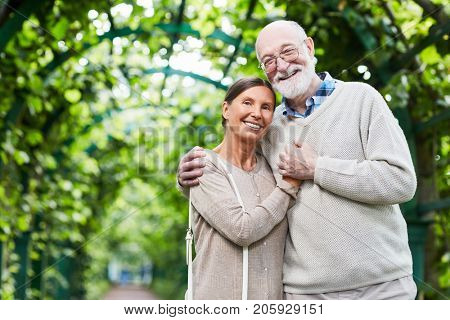 Devoted seniors in casualwear standing in embrace outdoors