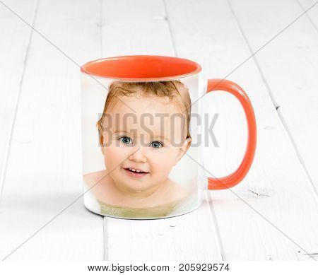 Small orange cup with bright orange handle and a printed face of a baby