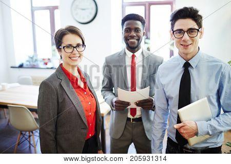 Successful employees in elegant formalwear looking at camera