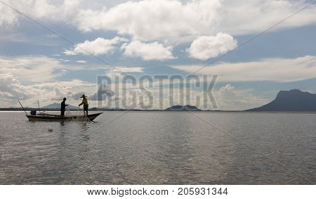 Two People Fishing With Net From A Boat In Sarawak, Borneo