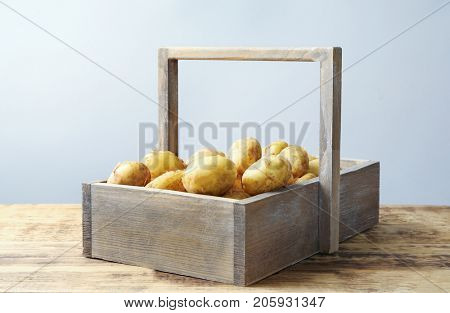 Wooden basket with young potatoes on table