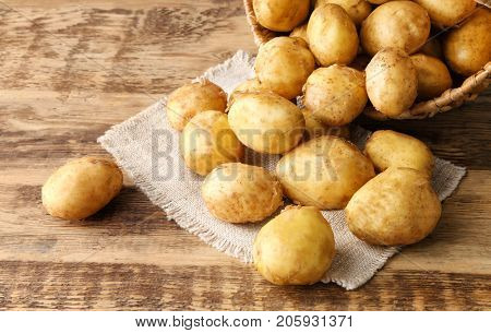 Wicker basket and young potatoes on wooden table