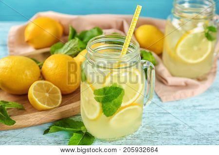 Jar of lemon juice and fresh lemons on table