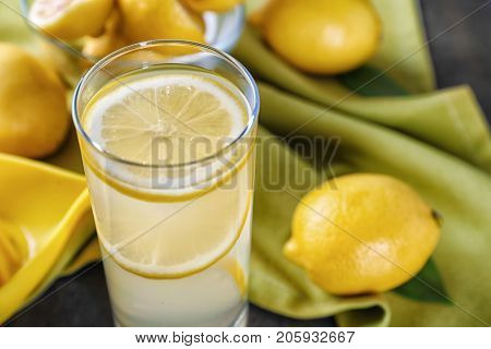 Composition with glass of lemon juice and fresh lemons on table, closeup