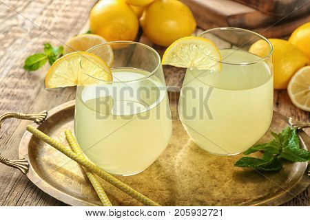 Two glasses of lemon juice and fresh lemons on wooden table