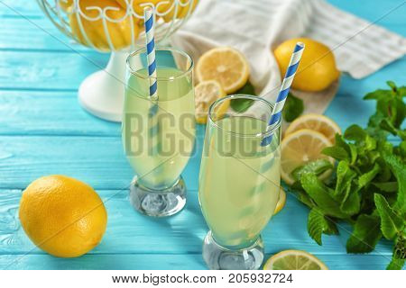 Composition with glasses of lemon juice and fresh lemons on table