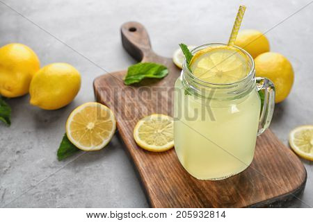 Composition with jar of lemon juice and fresh lemons on table
