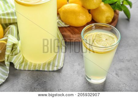 Glass of lemon juice with fresh lemons on table
