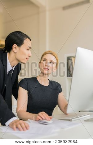 Contemporary economists working in front of computer in office