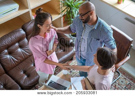 Businessman introducing teo women to one another while they handshaking
