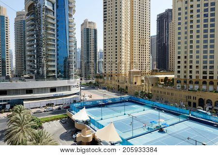 DUBAI UAE - SEPTEMBER 12: The Tennis courts near a Walk at Jumeirah Beach Residence on September 12 2013 in Dubai United Arab Emirates. In the city of artificial channel length of 3 kilometers along the Persian Gulf.
