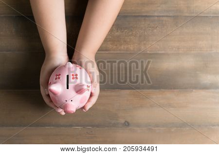 Kid Hold A Pig Bank On The Vintage Wood Background