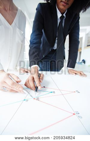 Two professionals pointing at graph on paper while discussing it