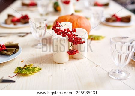 Candles, ripe ashberries and glasses on background of festive table
