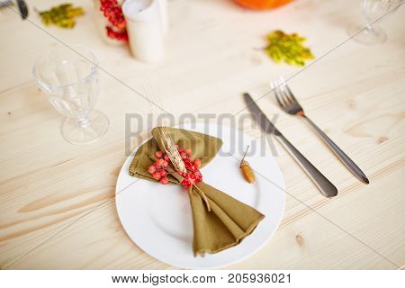 Napkin with wheat spike and ripe ashberries tied by red ribbon and acorn on plate with empty glass, knife and fork on served wooden table