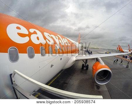 Amsterdam, Netherlands: January, 2015: Passengers board an Easy Jet airplane at Schiphol airport. Easy Jet is a British airline operating under the low-cost carrier model based at London Luton Airport
