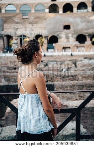 Rome, Italy - August 21, 2016: Young woman inside The Colosseum, also known as the Flavian Amphitheatre. It is an oval amphitheatre in the centre of the city of Rome.