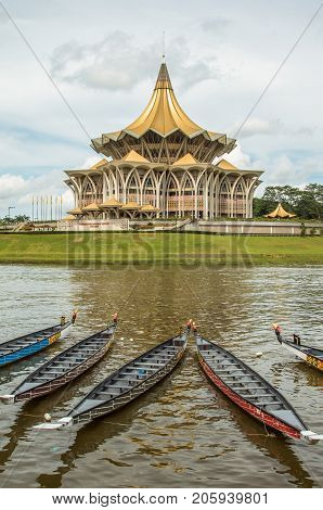 The new Parliament, Kuching, Sarawak, under the water festival in November 2016. Longboats lay on river in front of the building. Dramatic clouds behind.