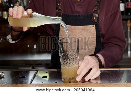 Professional bartender is pouring lemonade or ginger ale in mixing glass