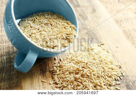 Cup of long grain brown rice on table