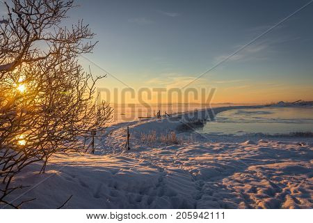 Winter landscape with snow, frozen ocean, ice, blue sky at sunrise in Norway, Fredrikstad, Nature Reserve. This is an important area for birds and bird watchers in Norway. January.