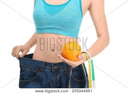 Young woman in oversized jeans with orange and measuring tape on white background. Diet concept