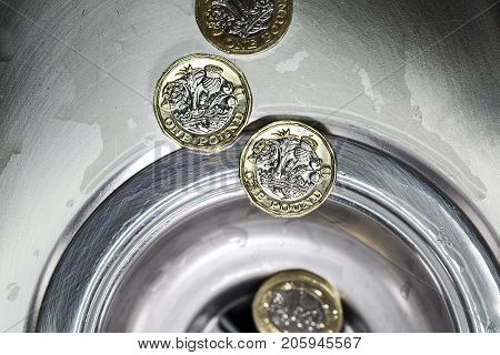 Four new 2017 one pound coins falling down a drain signifying a waste of money or loss.