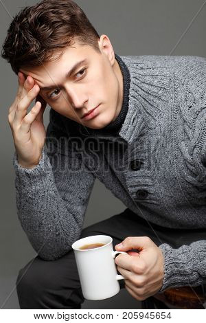 Sexy young man in warm knit sweateron with a cup of tea in his hands. Male model.