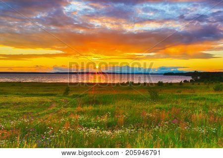 Sunset over the river Kama. Flowers meadow on the foreground