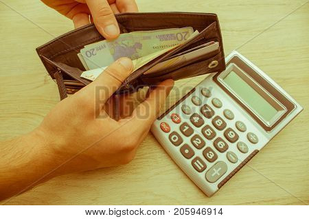 money with black wallet on the wooden table. Dealing with money. image of man holding wallet with banknotes - Retro color