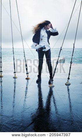 Fashion woman posing outdoor near ocean in windy day