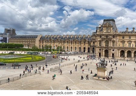 PARIS, FRANCE - JUNE 07, 2017: Louvre buildings and pyramid in main courtyard Cour Napoleon of Louvre Museum. Louvre Museum is one of largest and most visited museums worldwide.