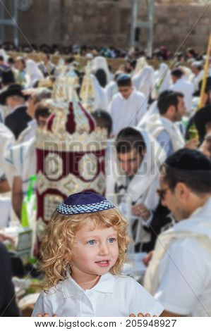 Handsome little boy with blond side curls and blue eyes, in skullcap. Autumn Jewish holiday Sukkot.  Western Wall of the Temple. Jerusalem, Israel