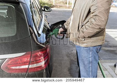 A man is refuelling his car at a self- service petrol station. He is using the green unleaded petrol nozzle.