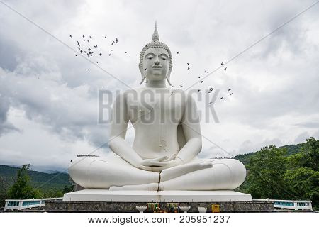 Outdoor large white Buddha Image in Buddhist temple where Buddhist to worship in Tak Thailand
