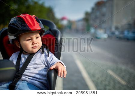 Family biking in the city. Little beautiful girl wearing helmets in bicycle seat. City on background