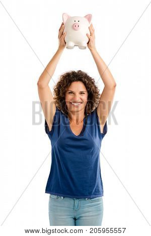 Portrait of a happy middle aged woman holding a Piggybank over her head