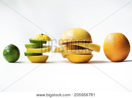 Closeup of oranges mixed with lime pieces isolated on white