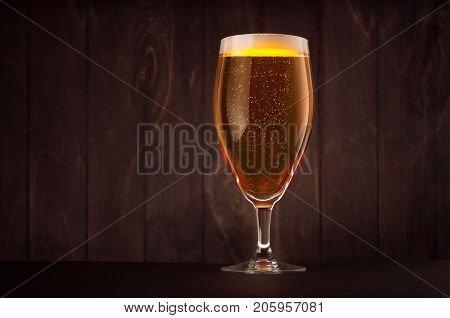 Goblet beer glass with golden sparkling lager on dark wood board copy space. Template for advertising design branding identity restaurant menu cover.