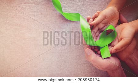 Adult and child hands holding Lime Green Ribbon panoramic banner background Mental health awareness and Lymphoma Awareness