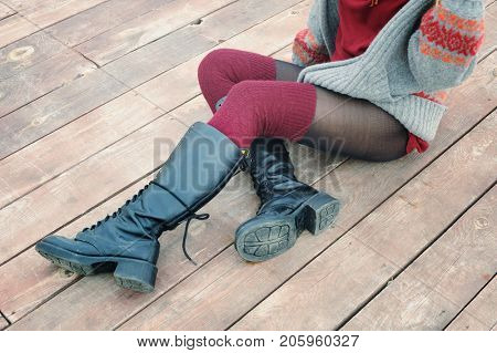 Female legs dressed in knee high boots and knitted stockings, woman sitting on a wooden planking, winter outdoor