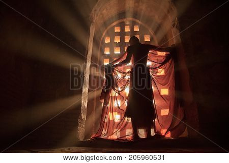 Myanmar novice monk standing in ancient temple with ray light on the sunset ,Bagan old town.