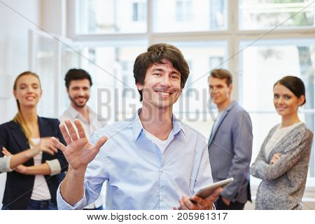 Succcessful young man as manager in front of business team
