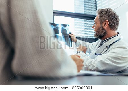 Doctor showing xray to his patient in medical office. Medical professional with patient sitting in examination room and discussing diagnosis of x-ray image.