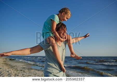 The young man gaily spends time with the little daughter on the sandy beach. Girl of 8-9 years sits on shoulders at the father and cheerfully smile. Against the background of the blue sky.