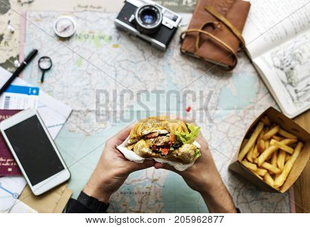 Closeup of hands holding hamburger over map background