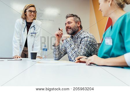 Positive medical team interacting at a meeting in hospital boardroom. Male and female healthcare workers during a medical briefing.